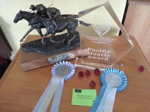 """My Writing Awards: From Top Left: Trophy for Best Practitioner Publication by an Equine Practitioner 2010 """"Equine Dentistry"""". Top right: Trophy and ribbon for Pacific Hearts Award 2014. Lower Left: ribbon for Finalist in Great Beginnings 2013."""