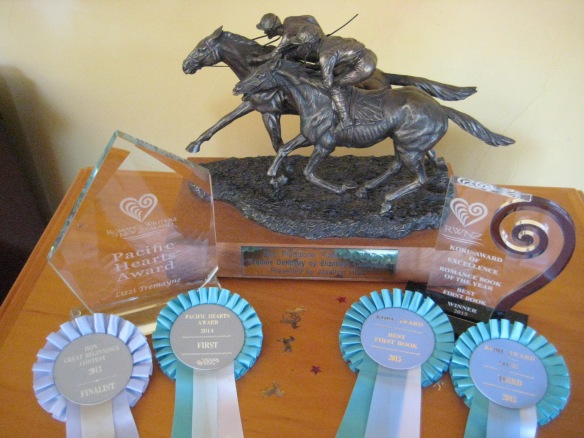 """My Writing Awards: From Top Left: Trophy for Pacific Hearts Award 2014, trophy for Best Practitioner Publication by an Equine Practitioner 2010 """"Equine Dentistry"""", trophy for Koru Award, Best First Book. From Bottom left: ribbons for Finalist in Great Beginnings 2013, Winner of Pacific Hearts 2014, Winner Koru Best First Book 2015 and Third Place Koru Best Long Book 2015."""